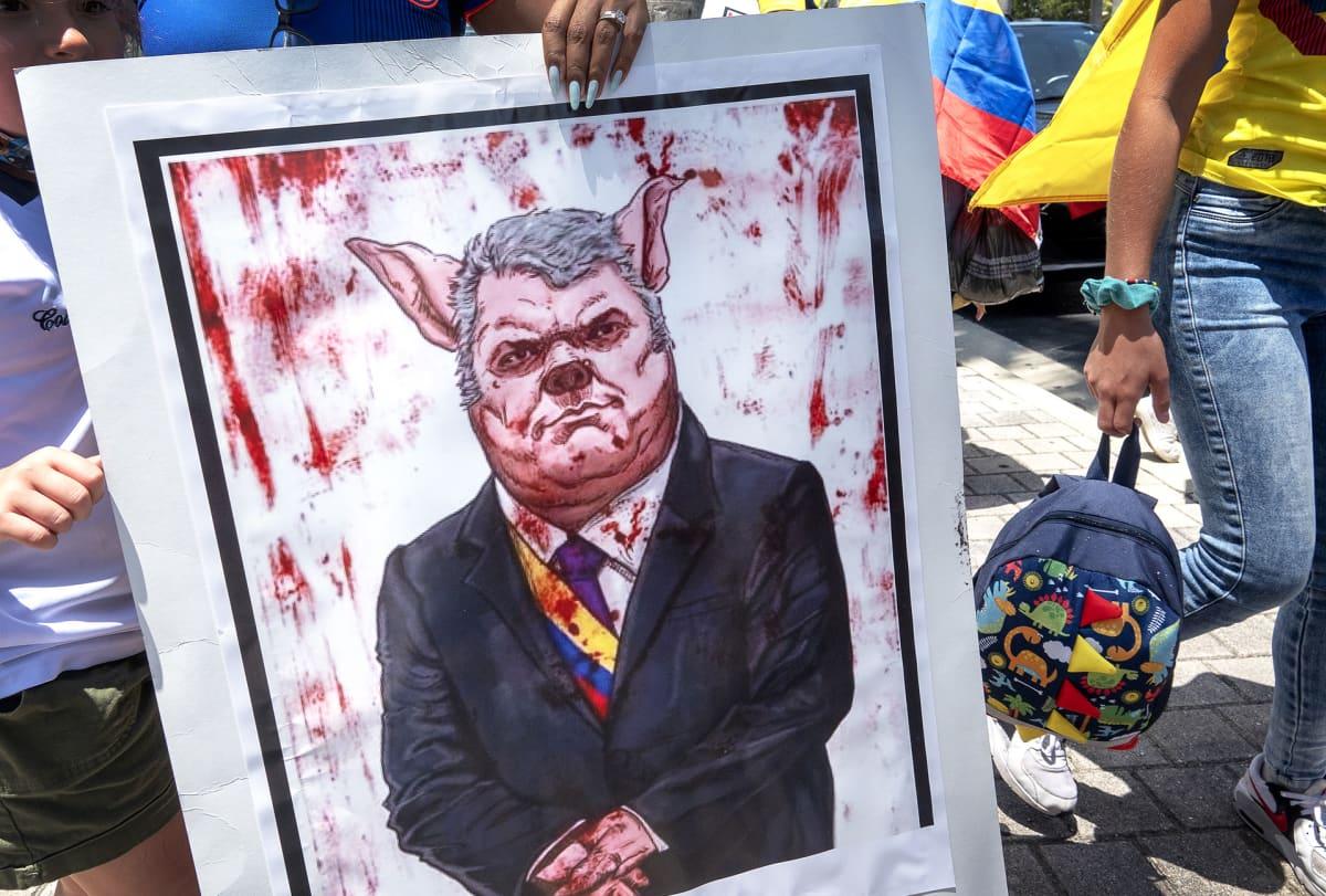 Kolumbialaismielenosoittajien maalama karikatyyri presidentti Iván Duquesta sikana.