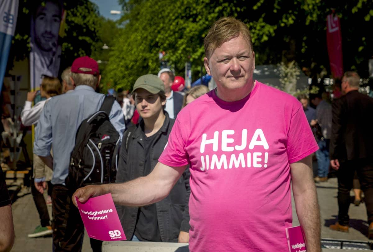 Miehellä on päällään pinkki Heja Jimmie! -paita.