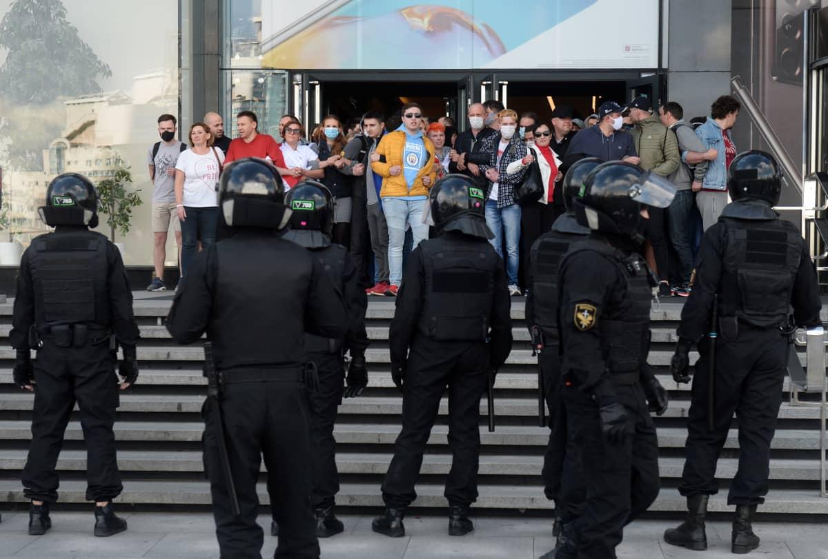Joukko mielenosoittajia seisoo portailla, vastapäätä rivi poliiseja selin kameraan