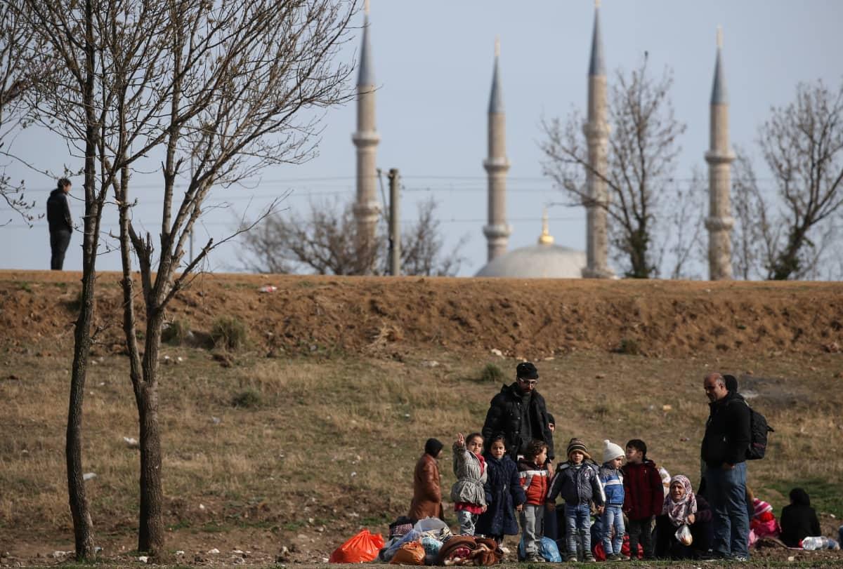 Turvapaikanhakijoita ulkona, taustalla näkyy moskeija.