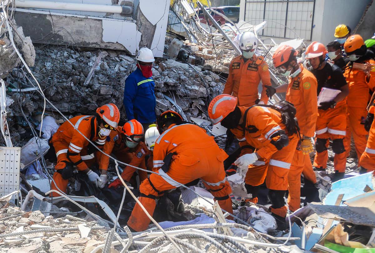 Pelastustyöntekijät etsivät uhreja romahtaneen hotellin raunioista.
