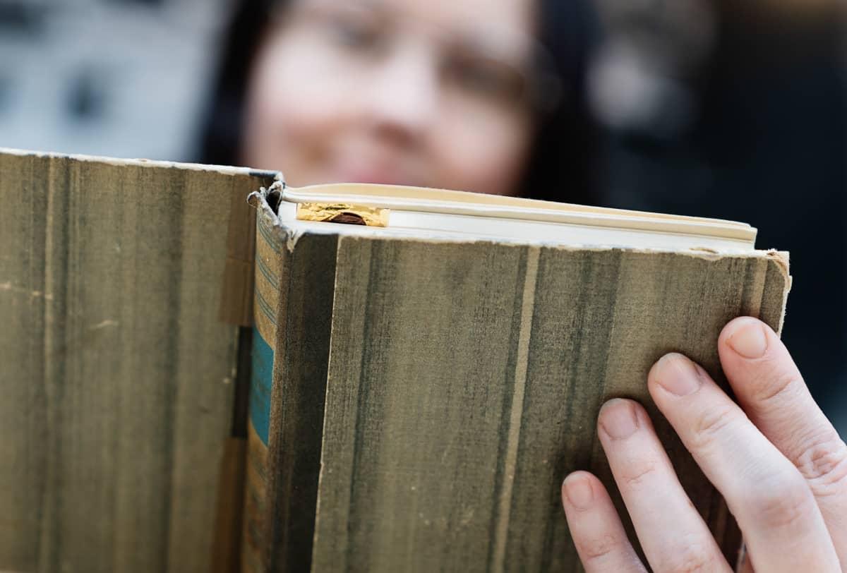 Kuvassa nainen selailee kirjaa.