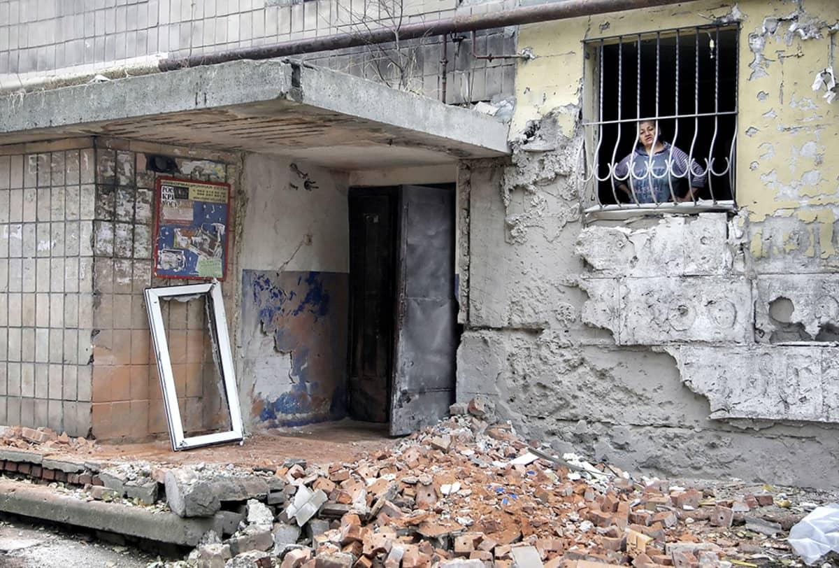 Nainen katsoo ikkunasta yöllisen tuhon jälkiä Donetskissa.