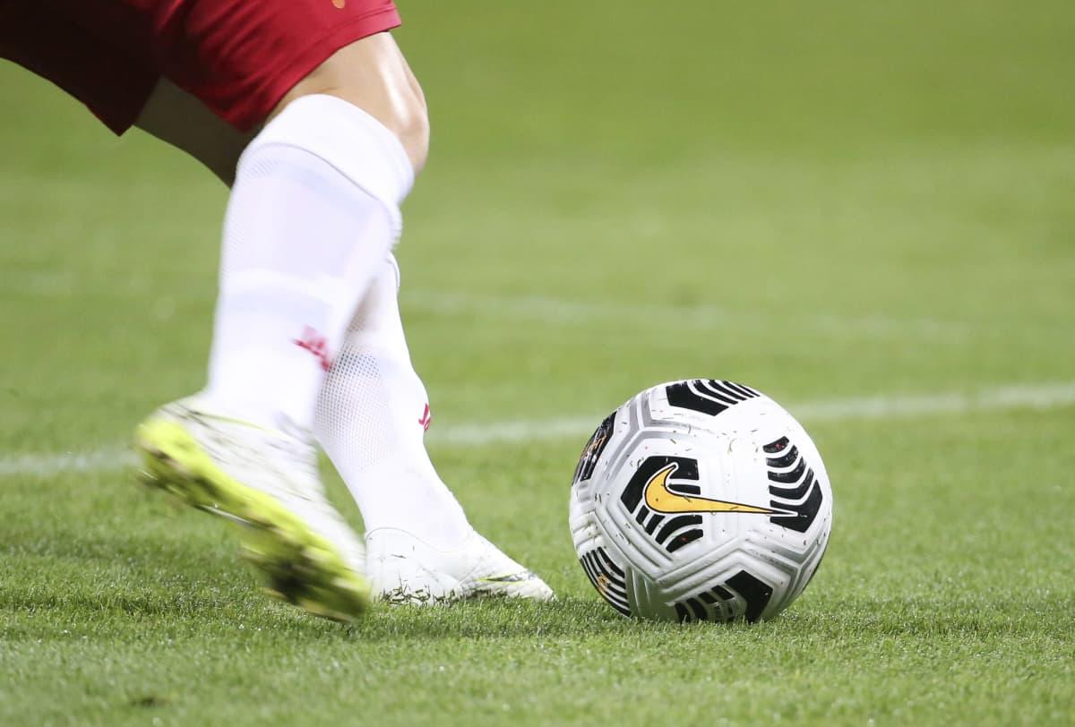 Nainen potkaisee jalkapalloa