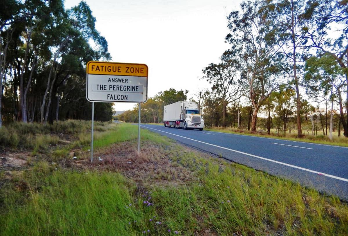 Kuvassa liikennemerkki, jossa kerrotaan, että maailman nopein eläin on muuttohaukka. Rekka on juuri tulossa merkin takaa.