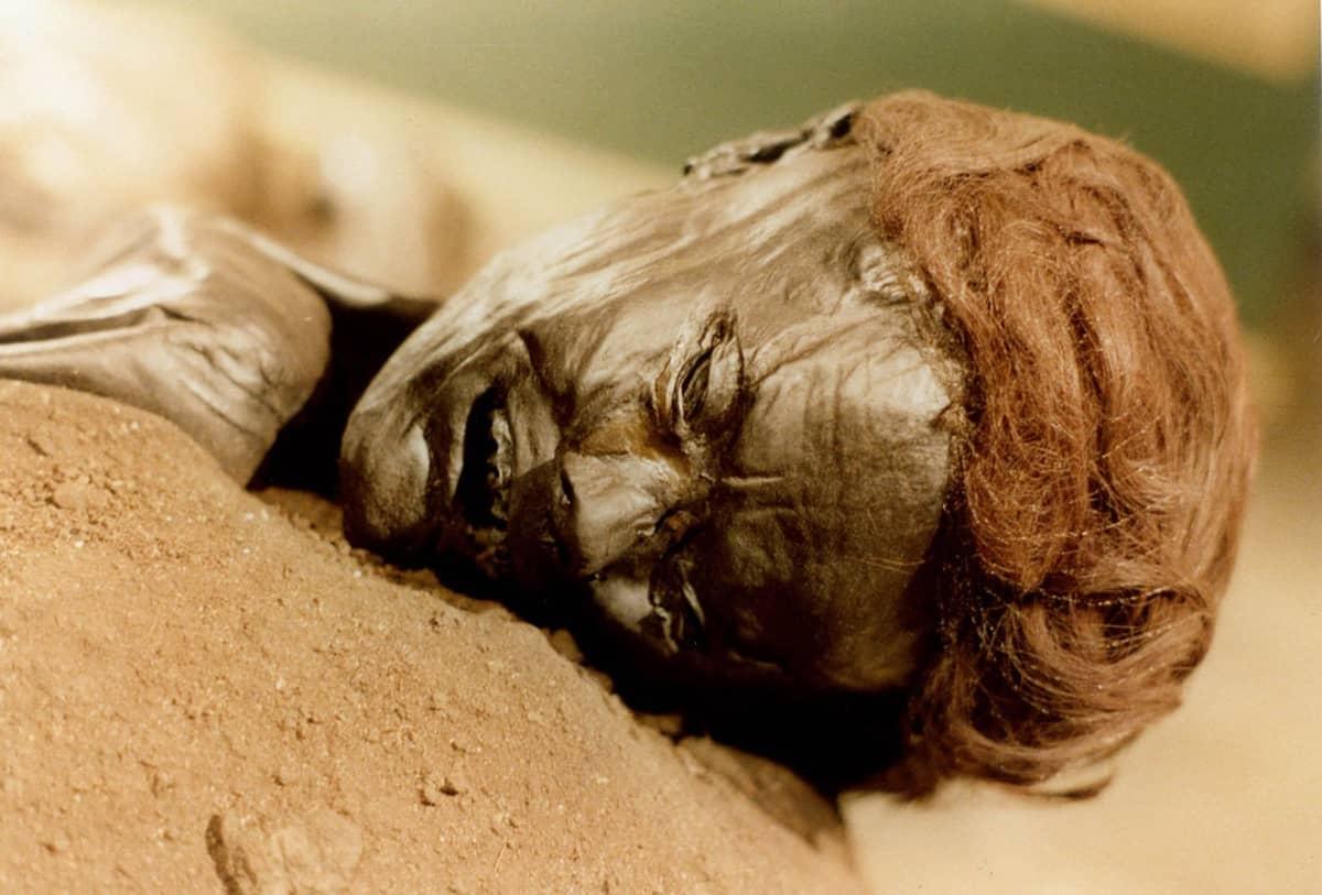 Hiekalla makaavan miesvainajan pää,  iho on suon tummentama, päässä punaiset hiukset.