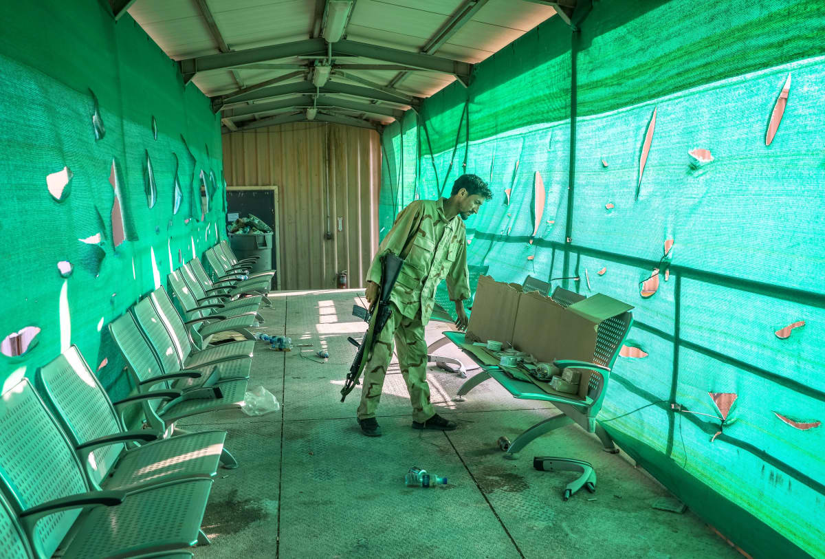 Afgaanisotilas seisoo vihreällä pressulla peitetyssä käytävässä ja tarkastelee penkkiä. Hänellä on toisessa kädessään jonkinlainen rynnäkkökivääri.
