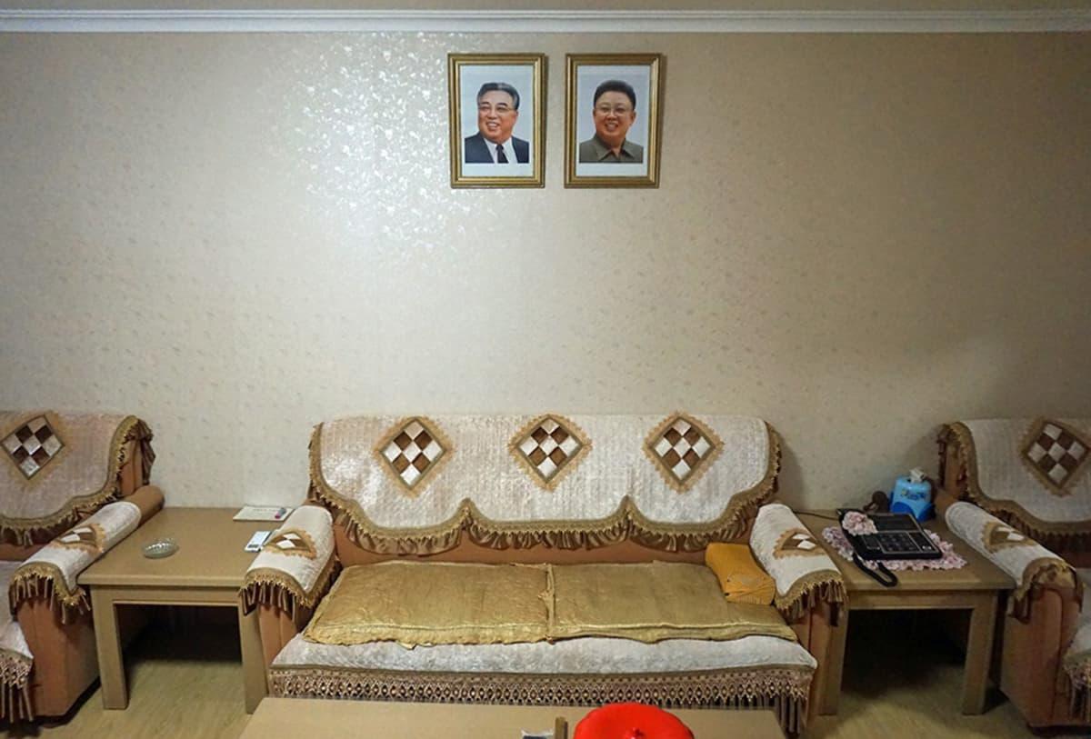 Olohuone seinällään johtajien kuvat. Maan entisten johtajien Kim Il-sungin ja Kim Jong-ilin kuvat koristavat Omin perheen olohuoneen seinää korkeammalla kuin mikään muu huoneessa. Kuvia on kohdeltava kodin arvokkaimpana omaisuutena. Poliisi voi tarkastaan niiden kunnon vaikka keskellä yötä.