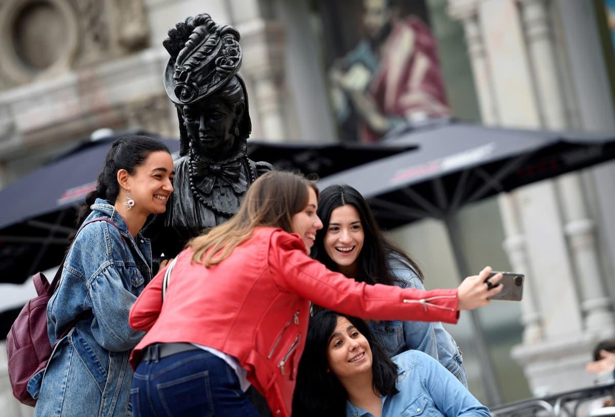 Naisia ottamassa ryhmäkuvaa patsaalla.