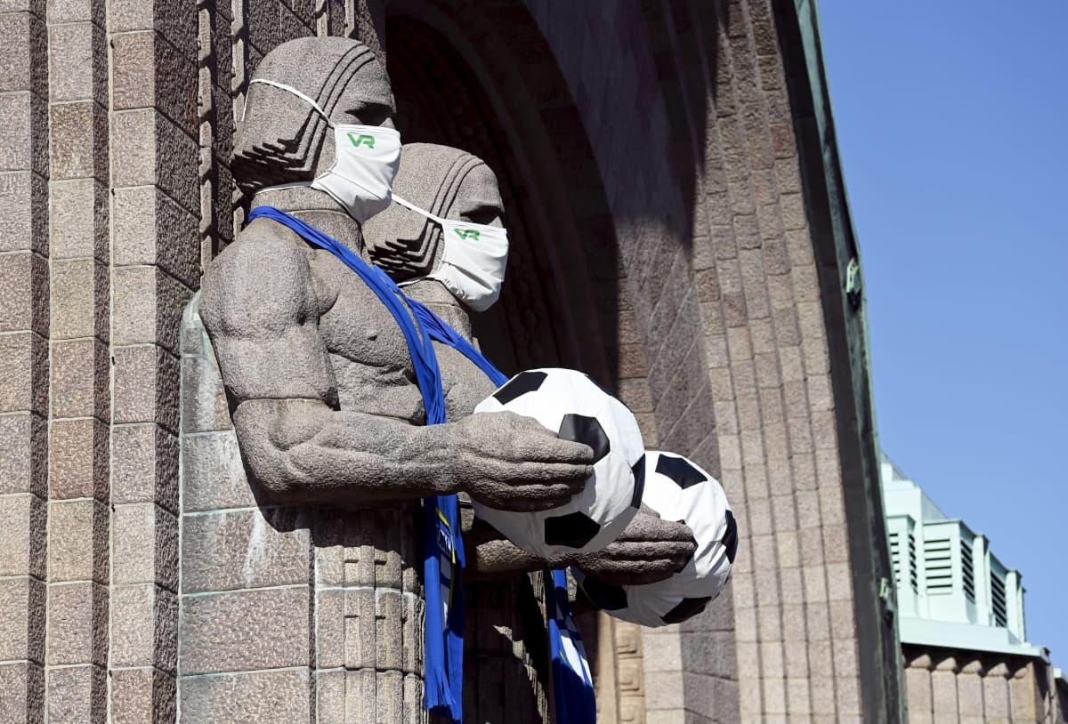 Helsingin päärautatieaseman kivimiehet kantavat jalkapalloja.
