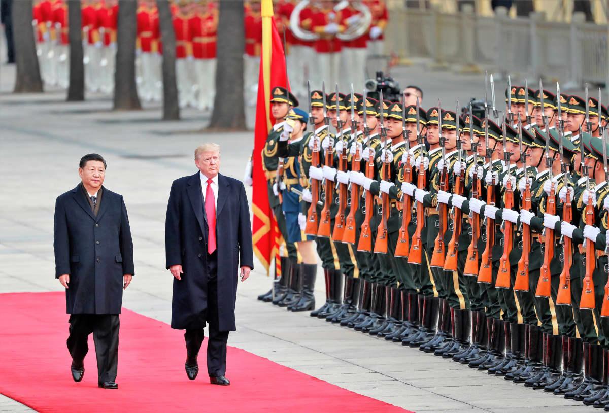 Presidentit Xi ja Trump kävelevät vakavina mustissa puvuissa ja päällystakeissa punaisella matolla kunniakaartin ohi. Xin päällystakki on napitettu, Trumpin päällystakki on auki ja kirkkaanpunainen kravatti näkyy koko pituudeltaan.