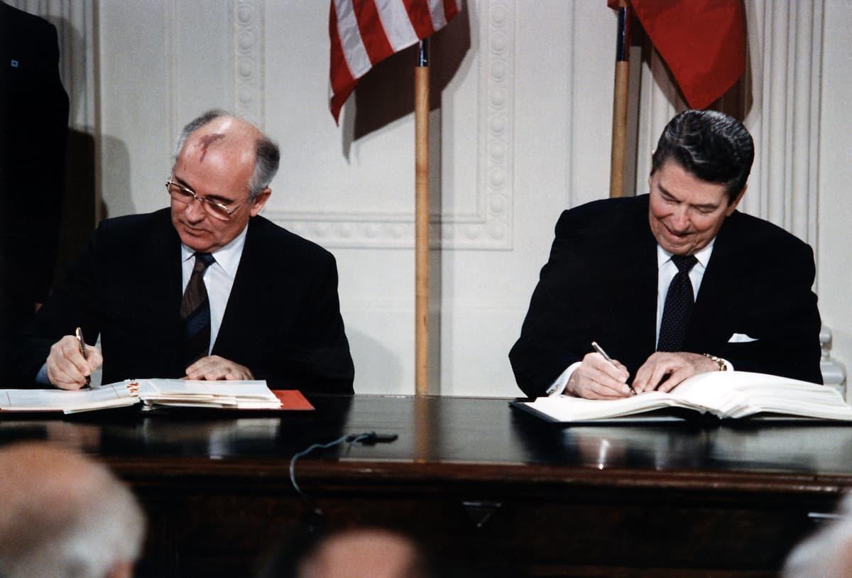 Gorbatšov ja Reagan istuvat pöydän takana ja allekirjoittavat sopimusasiakirjan kappaleita. Miehillä on mustat puvut ja kravatit. Taustalla seinällä ovat maiden liput.
