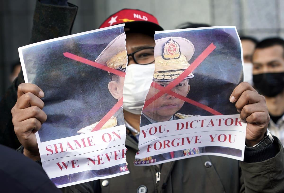 Japanissa asuva myanmarilainen osoittaa Tokiossa mieltään repimällä Min Aung Hlaingia esittävän kuvan.