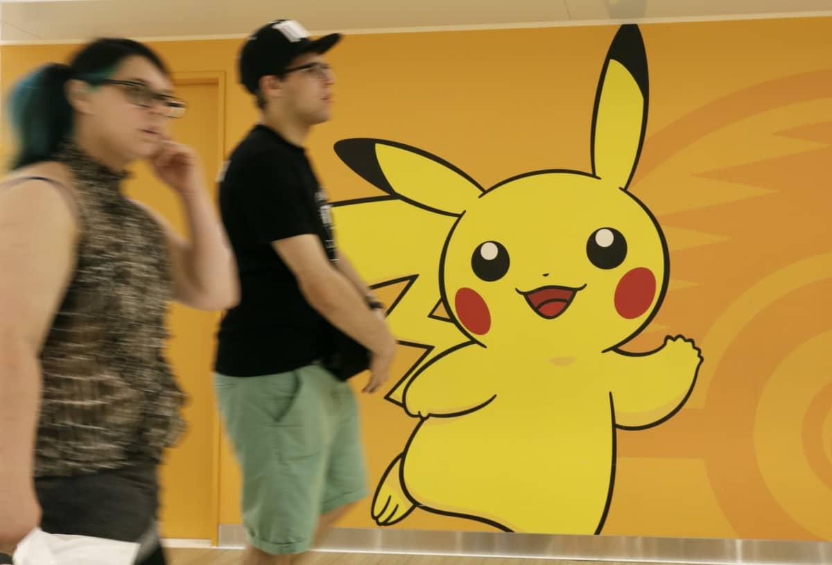 Turistit kävelevät seinään maalatun Pikachu-hahmon ohi Japanissa heinäkuussa 2016.