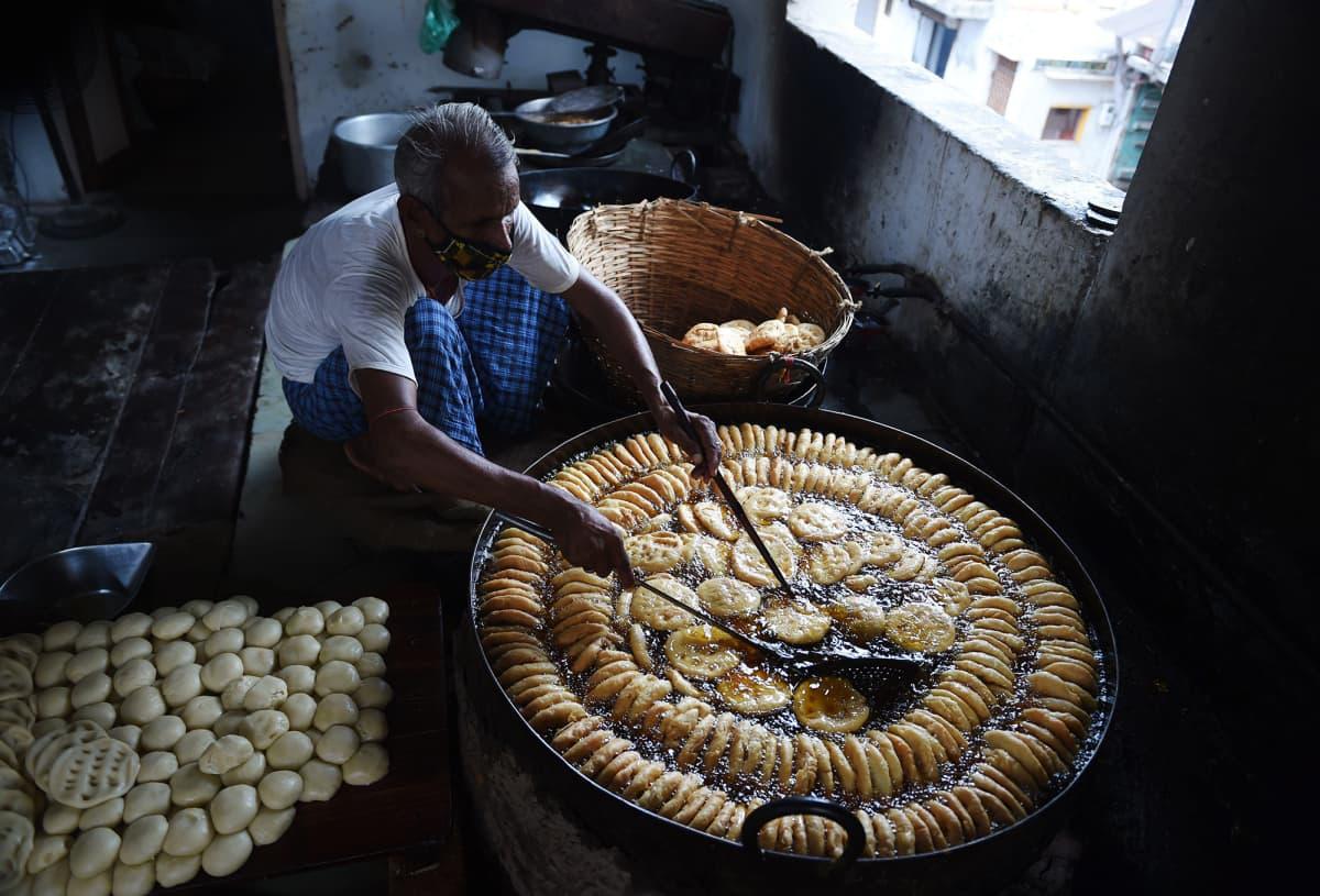 Kuvassa mies valmistaa makeisia Ahmedabadissa.