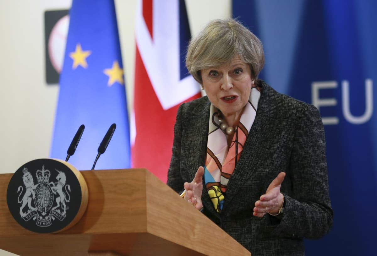 Britanian pääministeri Theresa May puhuu EU:n huippukokouksessa Brysselissä 09. maaliskuussa 2017. Taustalla EU:n ja Britannian liput.