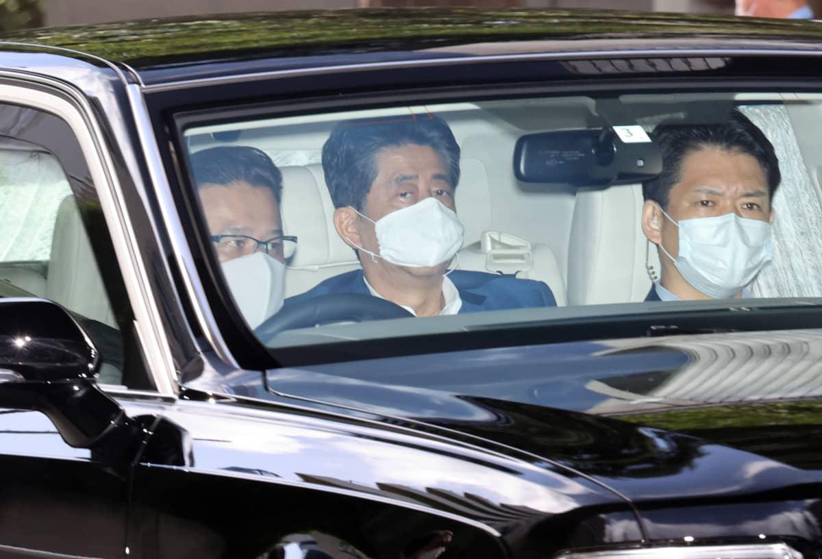 Shinzo Abe auton takapenkillä ikkunan läpi kuvattuna