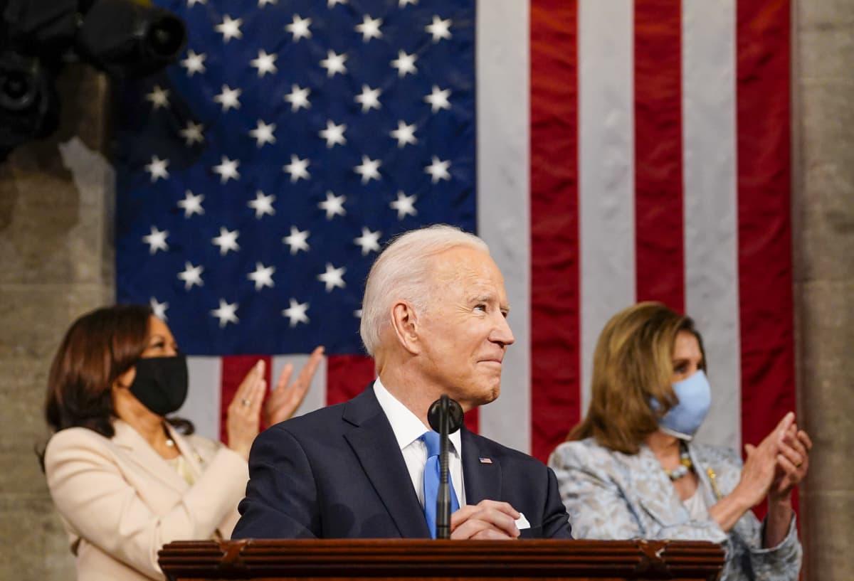 Joe Biden pitämässä puhetta, taustalla Kamala Harris ja Nancy Pelosi