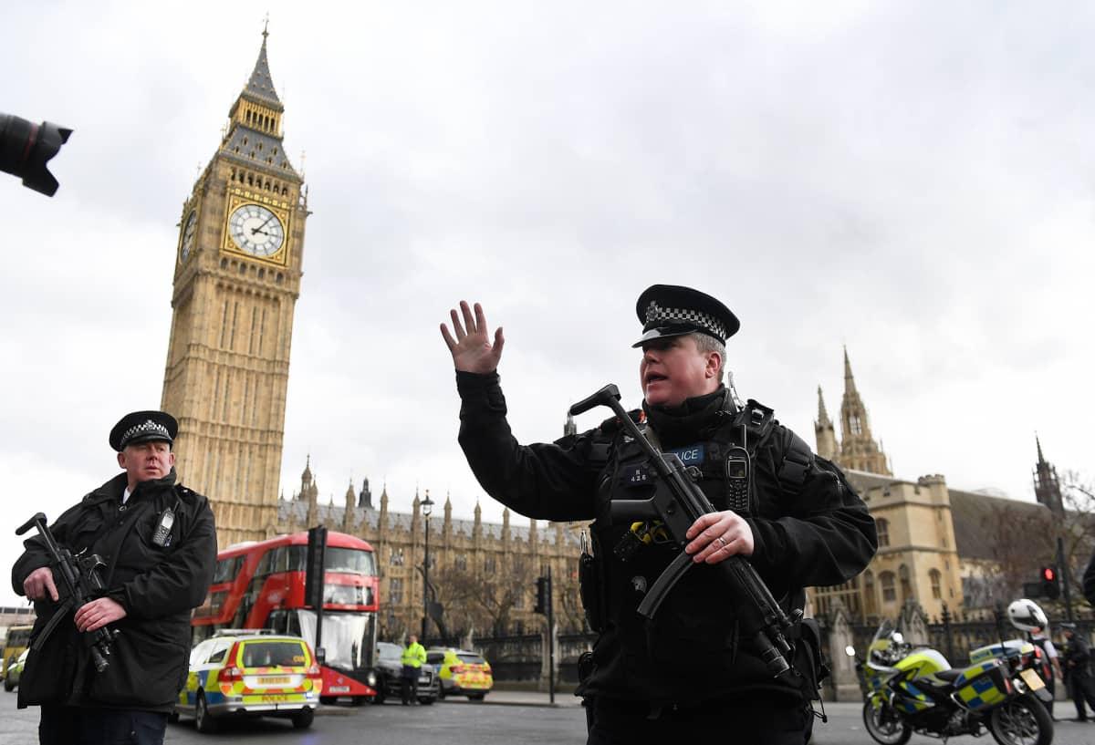 Aseistettu poliisi siirtää uteliaita kauemmas tapahtumapaikoilta.