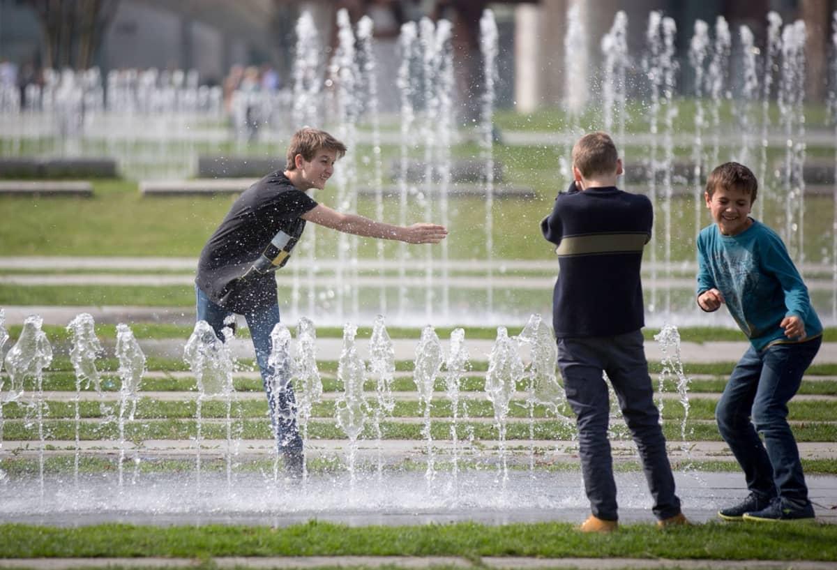 Kolme nuorta poikaa roiskuttaa vettä suihkulähteen reunalla.