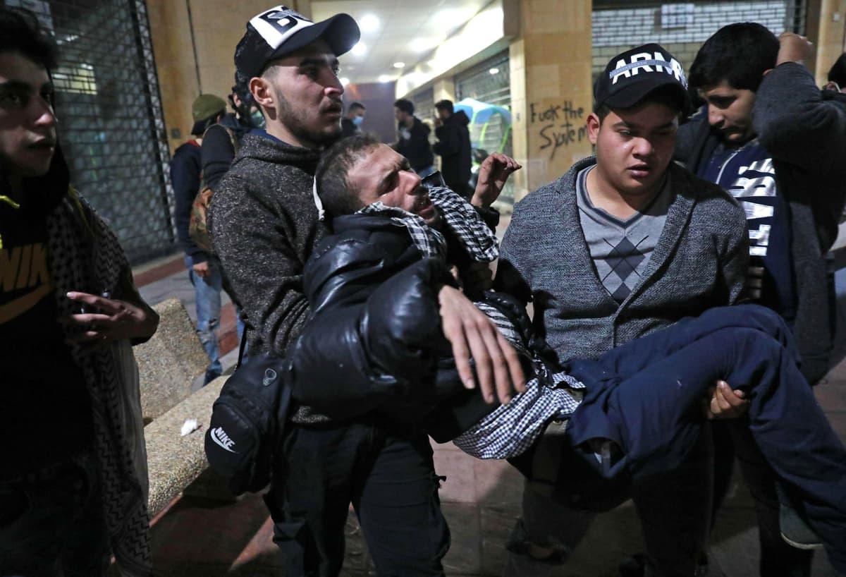 Kyynelkaasua hengittänyttä miestä kannettiin mielenosoituksessa Beirutissa 12. joulukuuta.