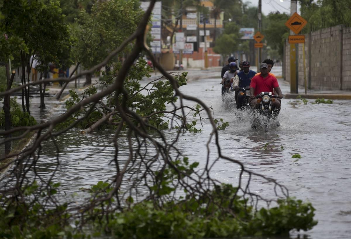 Moottoripyöräilijöitä tulvavedessä Puerto Ricossa