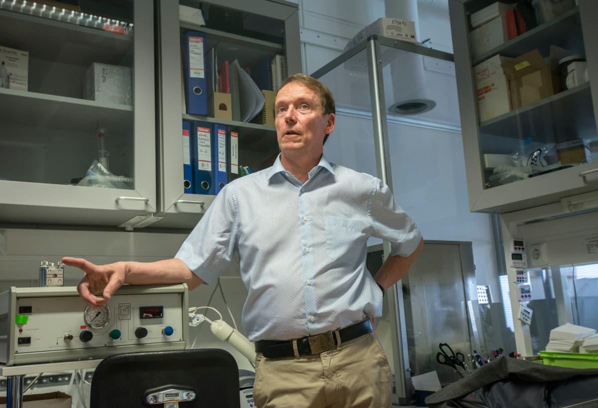 Professori puhuu toimittajalle laboratoriossa.