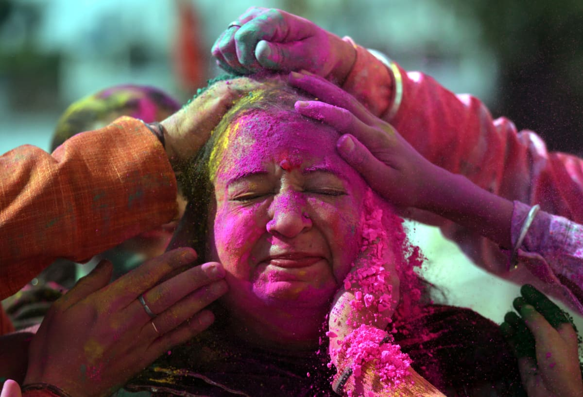 Naisen kasvoille levitetään punaista väriä.