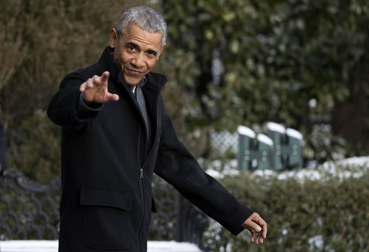 Barack Obama katsoo kameraan ja nostaa kättä tervehdykseksi.