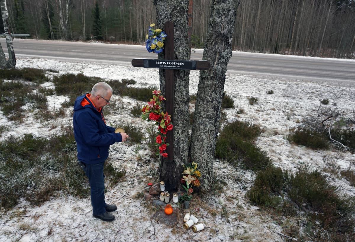 Juhani Tjurin sytyttää kynttilää muistomerkillä.
