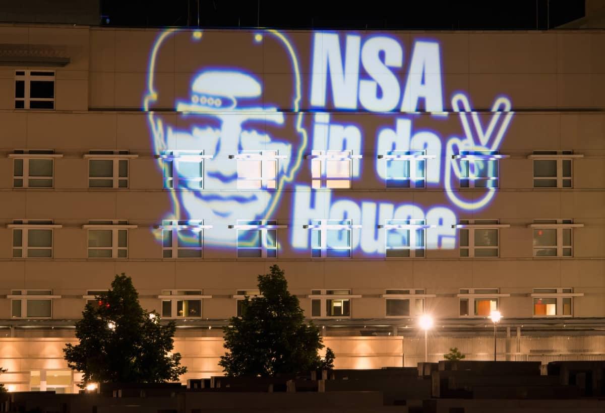 NSA on talossa -teksti (saksaksi) heijastettuna talon seinään