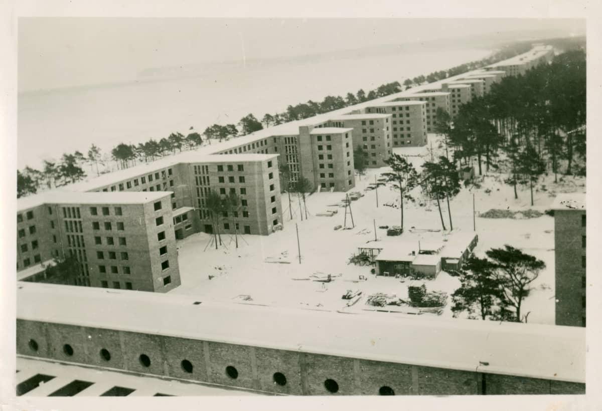 Vanha valokuva pitkästä rakennuksesta rannalla.