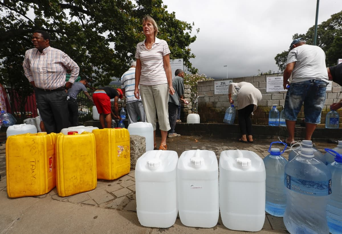 Kuvassa etualalla vesikanistereita, sitten kolme ihmistä seisomassa ja heidän takanaan ihmisiä hakemassa vettä vesipisteeltä Kapkaupungissa tammikuussa 2018.