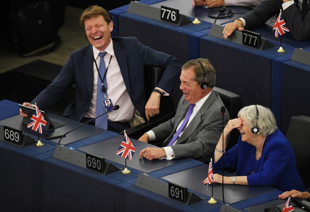 Brexit-puolueen Richard James Tice, Nigel Farage ja Ann Widdecombe naureskelivat istunnossa.
