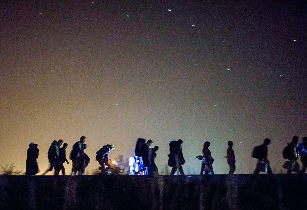 pakolaiset kävelevät jonossa yöllä