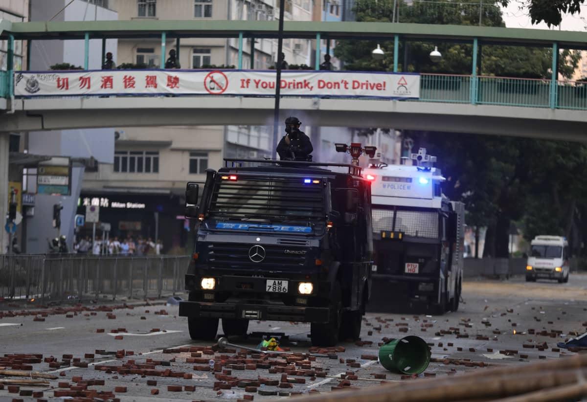 Poliisiajoneuvoja kivien täyttämällä kadulla.
