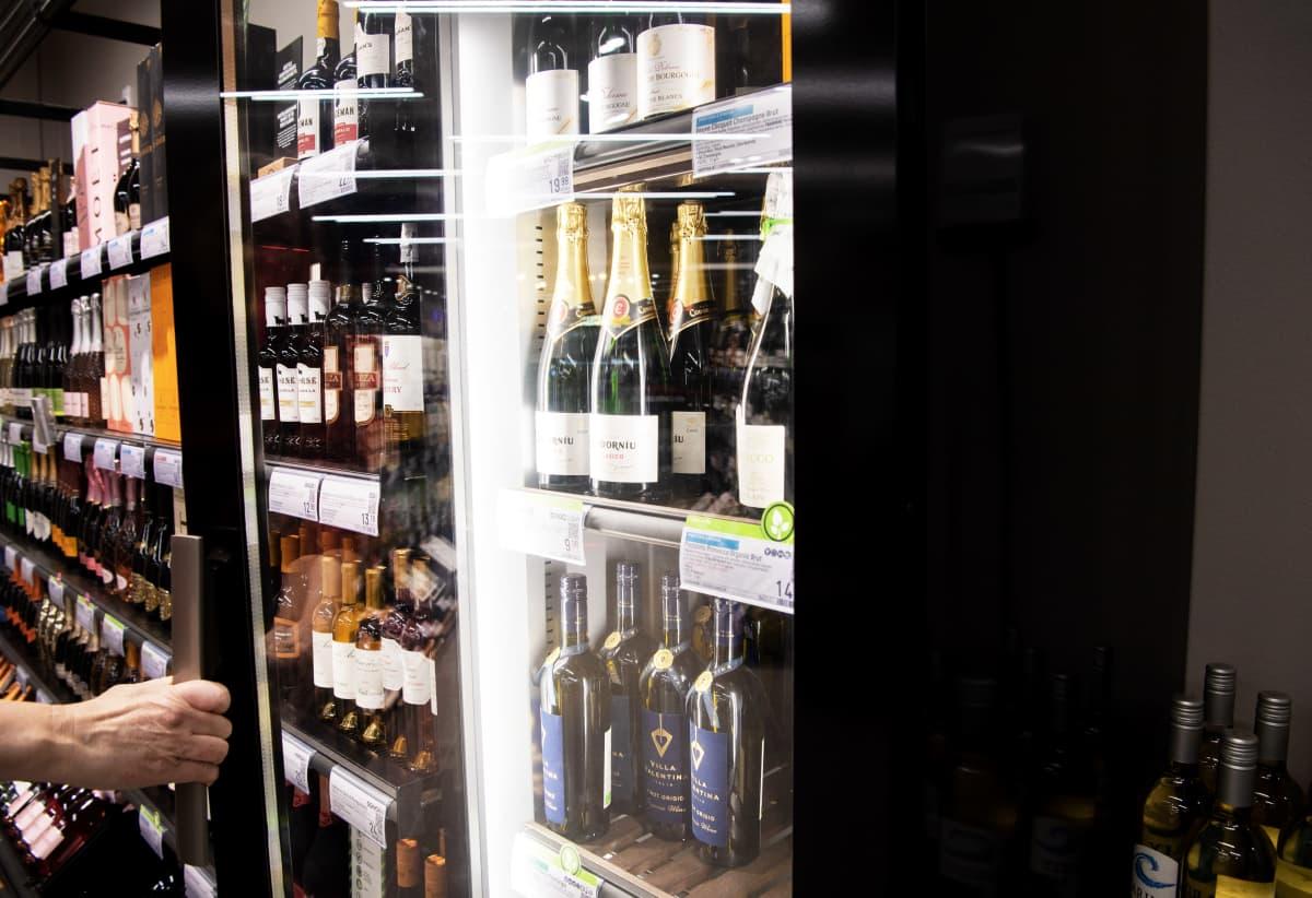 Asiakas avaa kylmäkaapin Alkossa.