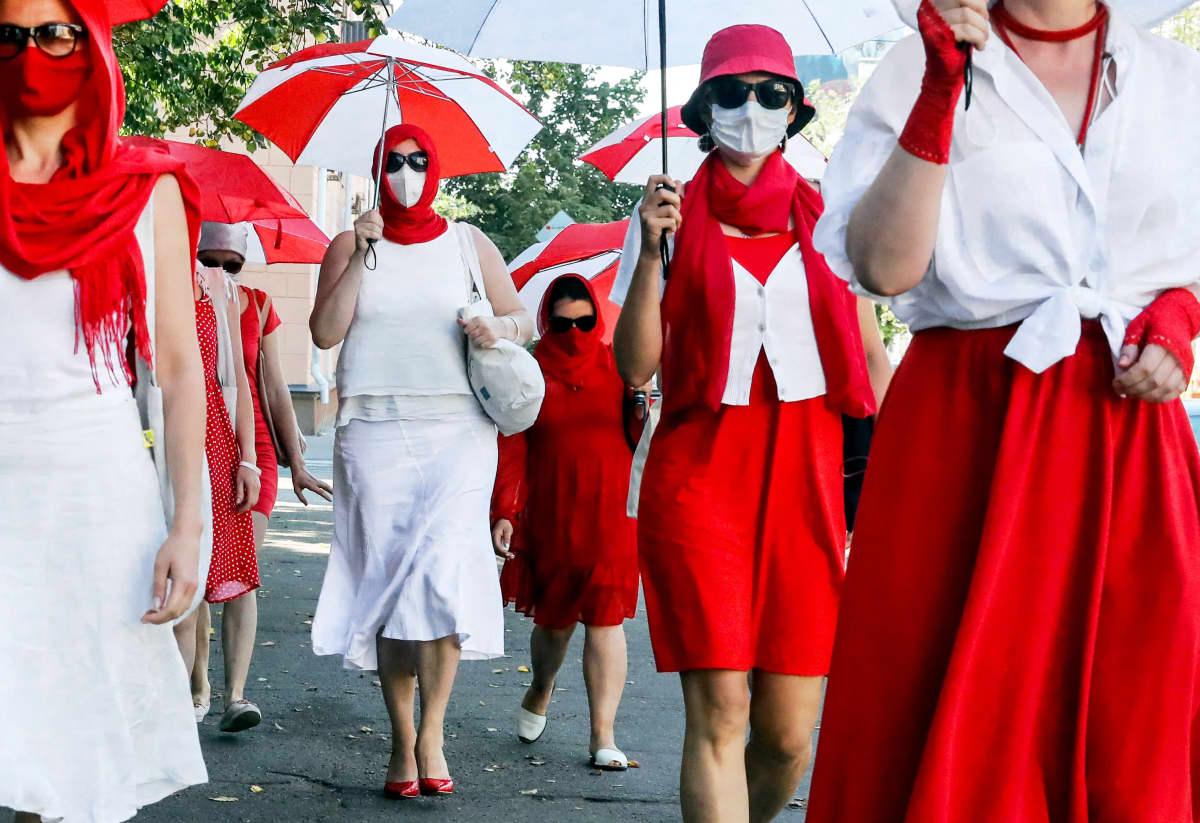 Valkovenäläisiä naisia osoittamassa mieltä kadulla punavalkoisiin pukeutuneena.