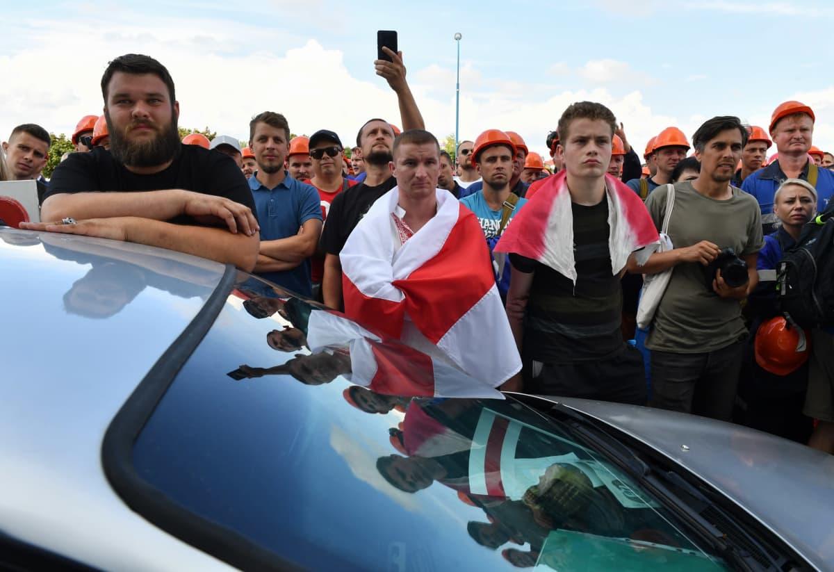 Suuri joukko miehiä seisoo auton luona. Parrakas mies nojaa auton kattoon. Yhdellä mieheillä on harteillaan punavalkoinen lippu.