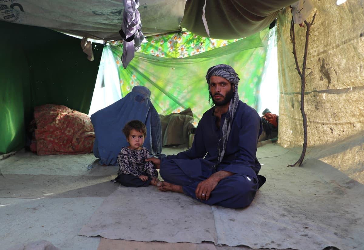 Mies, lapsi ja burkaan pukeutunut nainen istuvat teltassa pakolaisleirillä Kabulissa.
