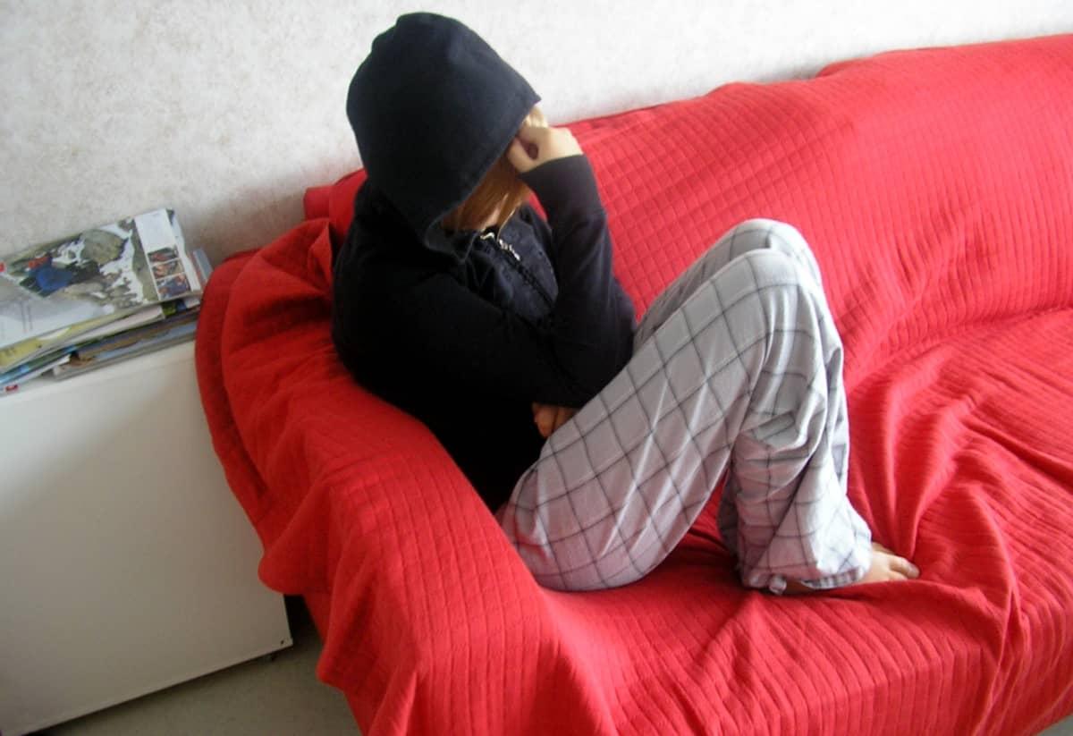 Nuori istuu yksin sohvalla.