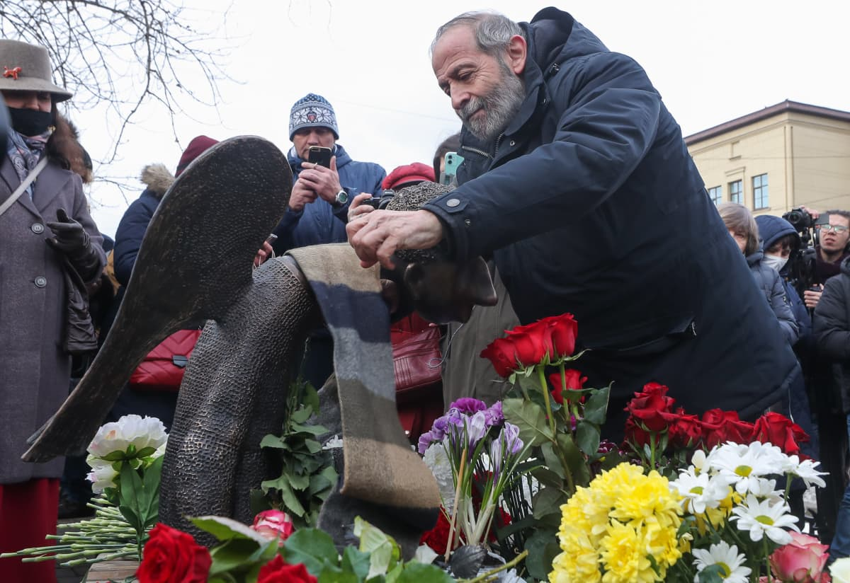 Parrakas mies Boris Vishnevski jättää kukkia enkelipatsaalle, ympärillä ihmisiä ja kukkia