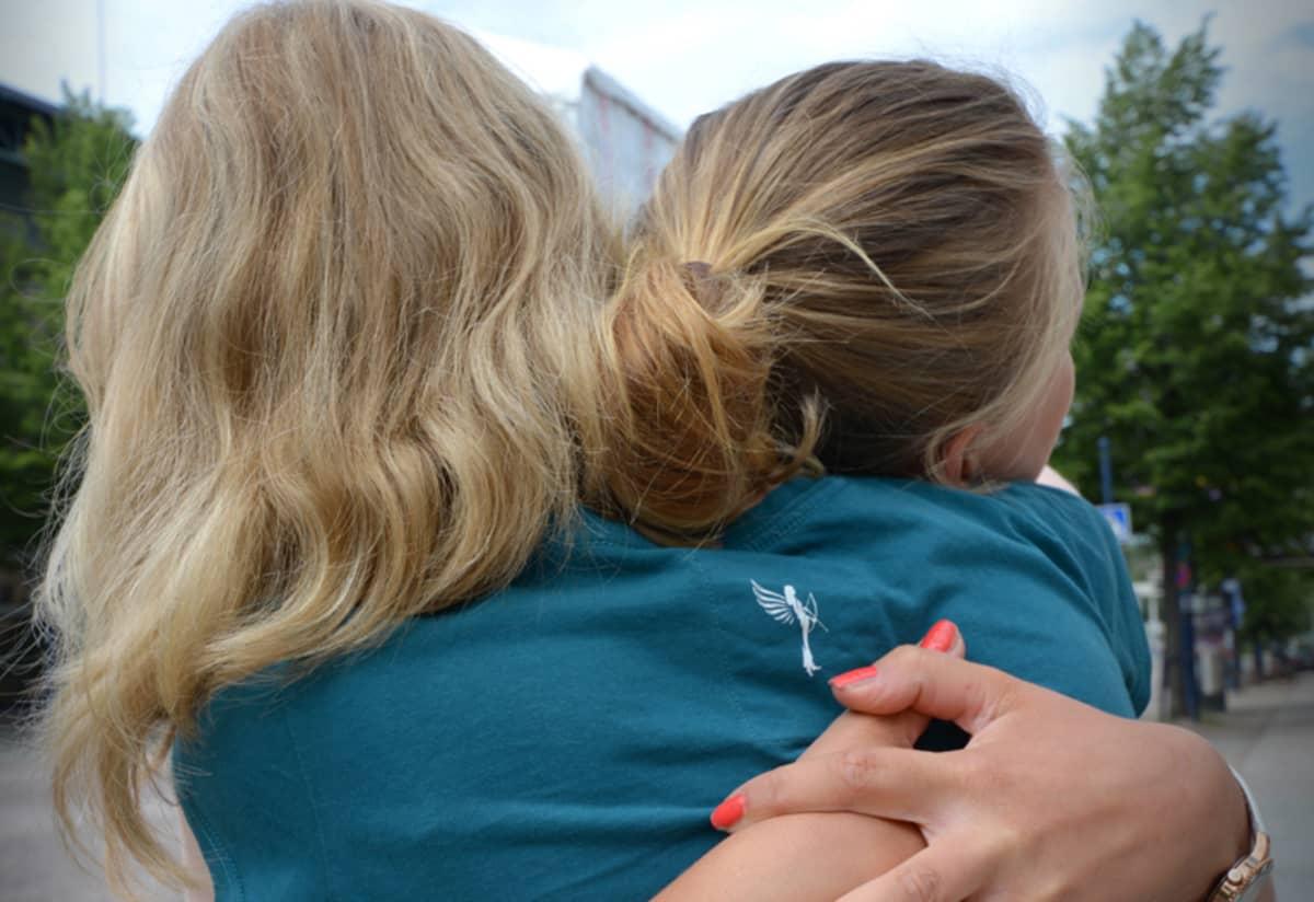 kaksi naista halaa.