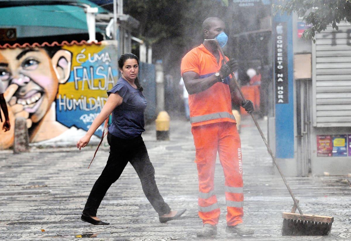 Hengityssuojaan pukeutunut mies lakaisee katua Rio de Janeirossa.