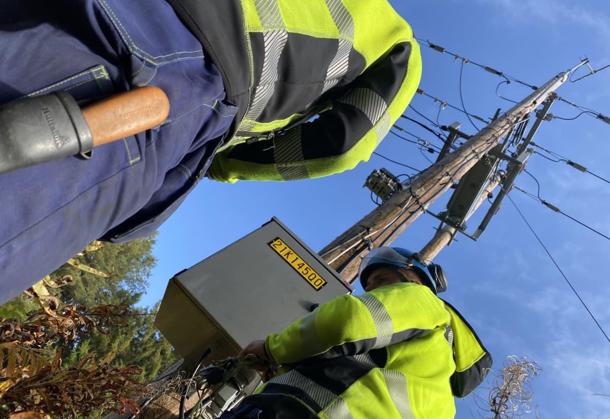 Sähköasentaja korjaamassa myrskytuhoja