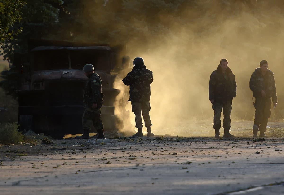 Ukrainalaissotilaat tarkastivat öisessä armeijan tarkastuspisteelle suunnatussa hyökkäyksessä tuhoutunutta armeijan ajoneuvoa Mariupolin lähistöllä 7. syyskuuta 2014.