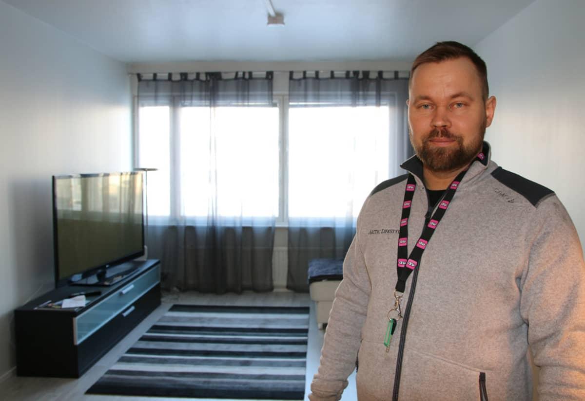 Yrittäjä JP Mikkola seisoo Airbnb:ssä vuokralla olevan kolmionsa olohuoneessa.