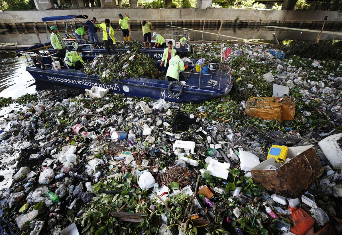 Kuvassa kerätään jätettä vedestä Thaimaassa.
