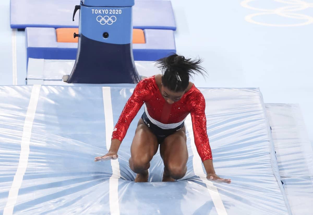 Simone Biles horjahtaa eteenpäin alastulossaan.