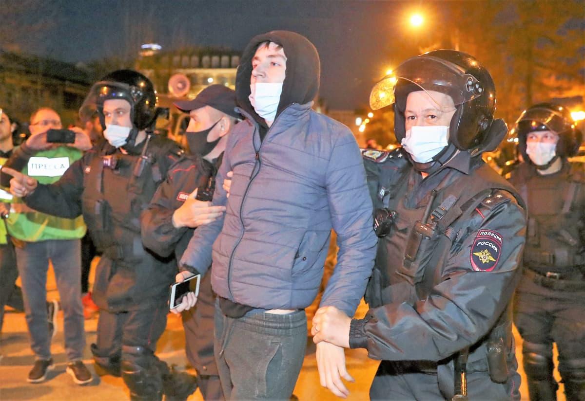 Mellakkavarusteisiin pukeutuneet poliisit kuljettavat keskellään huppupäistä nuorta miestä. On ilta. Taustalla keltaisiin huomiliiveihin pukeutunut mies kuvaa tilannetta kännykällään.
